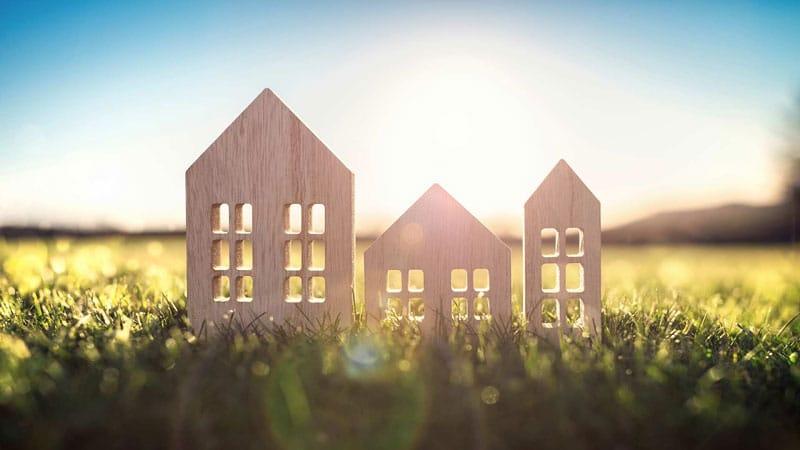 3 Dekoholzhaeuser in Wiese als Sinnbild fuer Bauen mit Holz